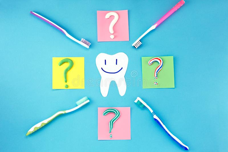 Symbol of question mark from toothpaste and toothbrush on blue background,. Toothpaste selection concept. Concept of dental care. Cleaning teeth stock photography