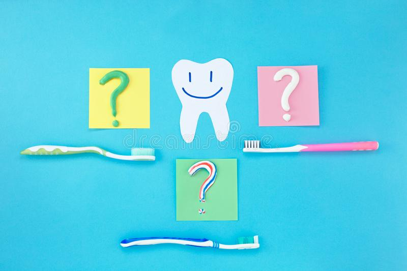 Symbol of question mark from toothpaste and toothbrush on blue background,. Toothpaste selection concept. Concept of dental care. Cleaning teeth stock image
