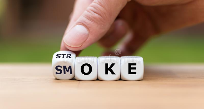 Symbol for the risk of smoking. Hand turns a dice and changes the word `stroke` to `smoke`. royalty free stock photography