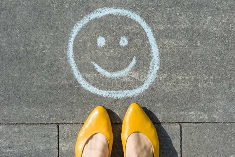 Symbol rysujący na asfaltu i kobiety ciekach szczęśliwy smiley obraz stock