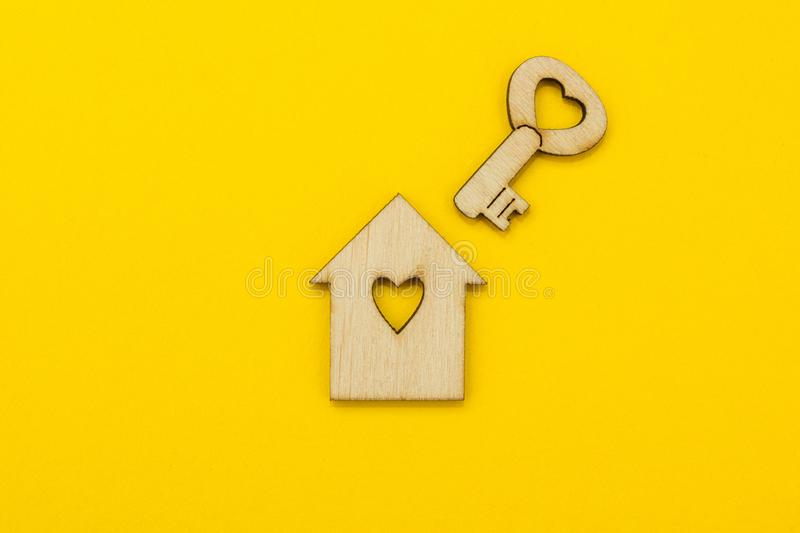 Symbol of a small house and a key with a heart on a yellow background stock photography