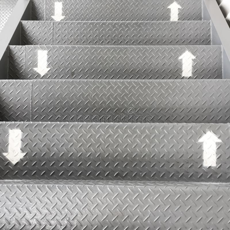 The symbol of the way up and down on the stairs. The arrows were painted in white on the stainless steel ladder. It is direction stock photos