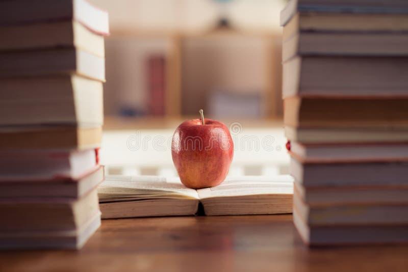 Symbol of wisdom. Red apple between book stacks as a symbol of wisdom stock photos