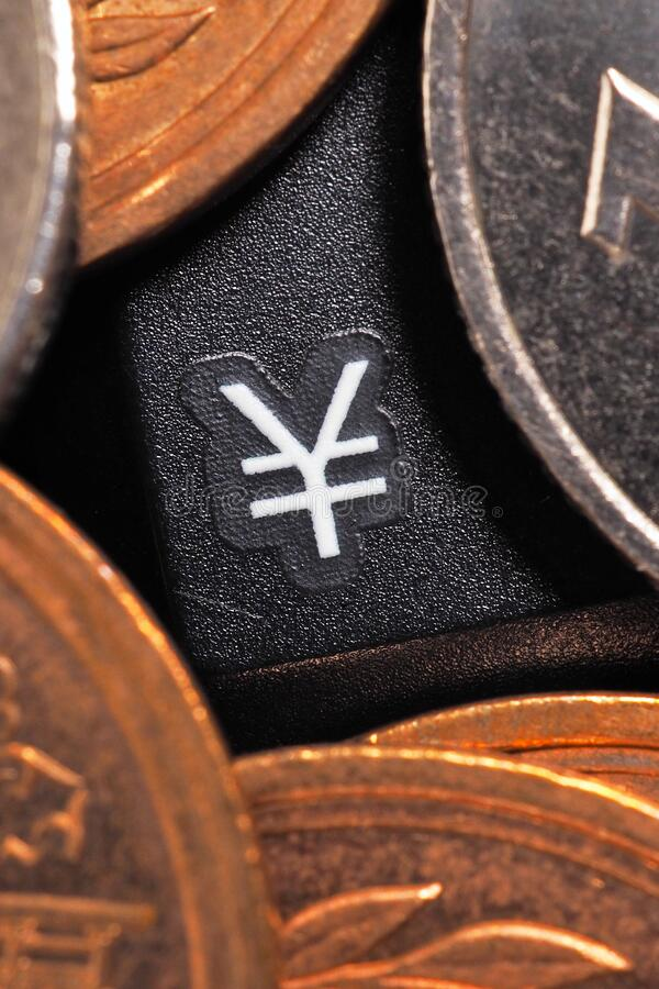 The symbol of the yen. Japanese money coins lie on a black computer or laptop keyboard around a button with this sign. Online trading, payments and transfers stock image
