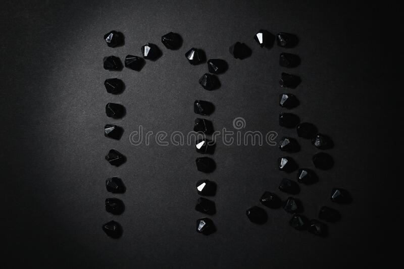 Symbol of the zodiac sign Virgo made by black stones. Low dark key. Symbol of the zodiac sign Virgo made by black stones on a black background. Low dark key stock images