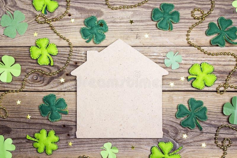 Symbole à la maison chanceux avec le trèfle à quatre feuilles sur le fond en bois Co photos libres de droits