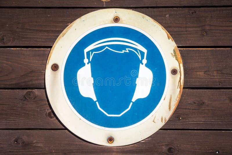 Symbole bleu de manchon d'oreille sur la texture en bois photos stock