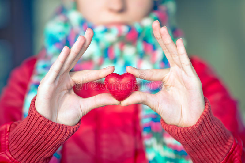 Symbole d'amour de forme de coeur chez des mains de la femme avec le visage sur le fond photographie stock