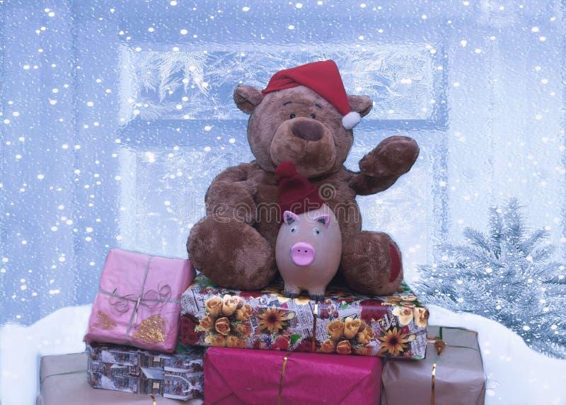 Symbole d'ours et de porc de Noël de 2019 se reposant sur une montagne des cadeaux photos libres de droits