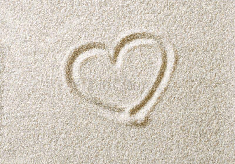 Symbole de coeur dessiné en photo de macro de surface de sable photos libres de droits