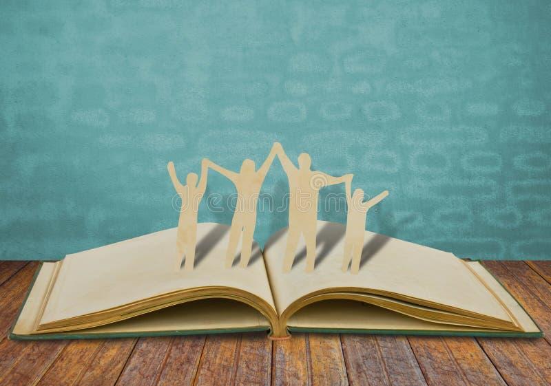 Symbole de famille de coupe de papier sur le vieux livre photographie stock
