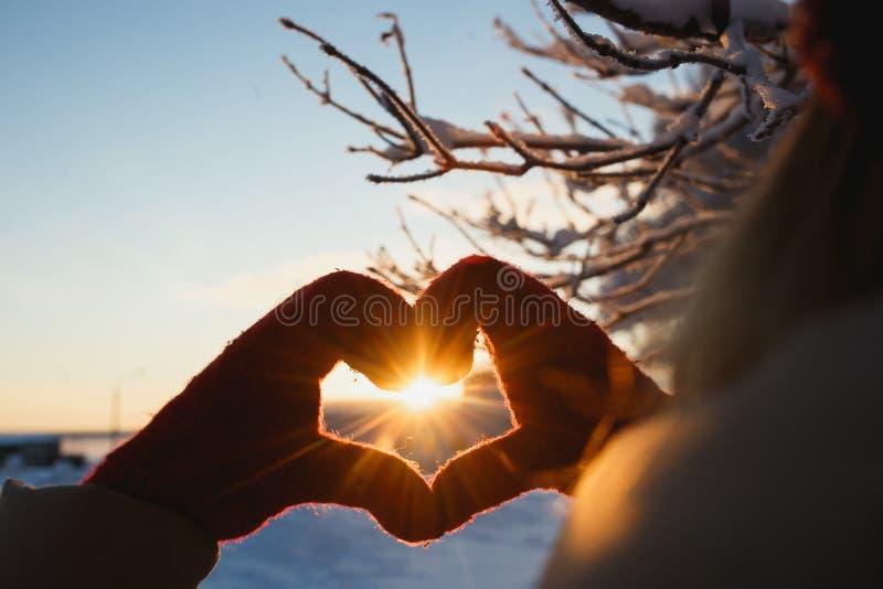 Symbole de forme de coeur des mitaines de femmes dans le coucher du soleil givré d'hiver Concept de l'hiver, de la datation, du j photo libre de droits