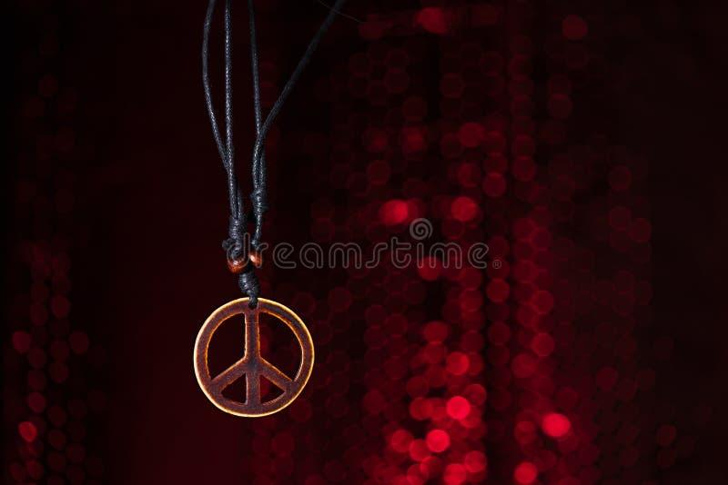 Symbole de paix en bois avec le fond de lumières rouges photos stock