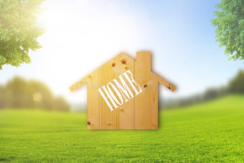 Symbole ? la maison dans le paysage avec le pr? vert image libre de droits