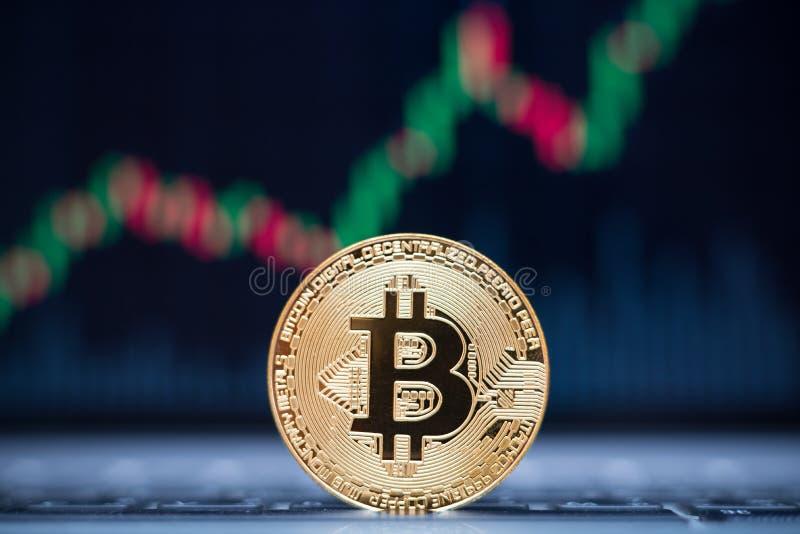 Symbole physique de pièce de monnaie de Bitcoin sur l'ordinateur portable avec le fond de graphique des prix de tendance à la hau images libres de droits