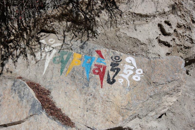 Symbole religieux népalais écrivant sur une roche photographie stock libre de droits