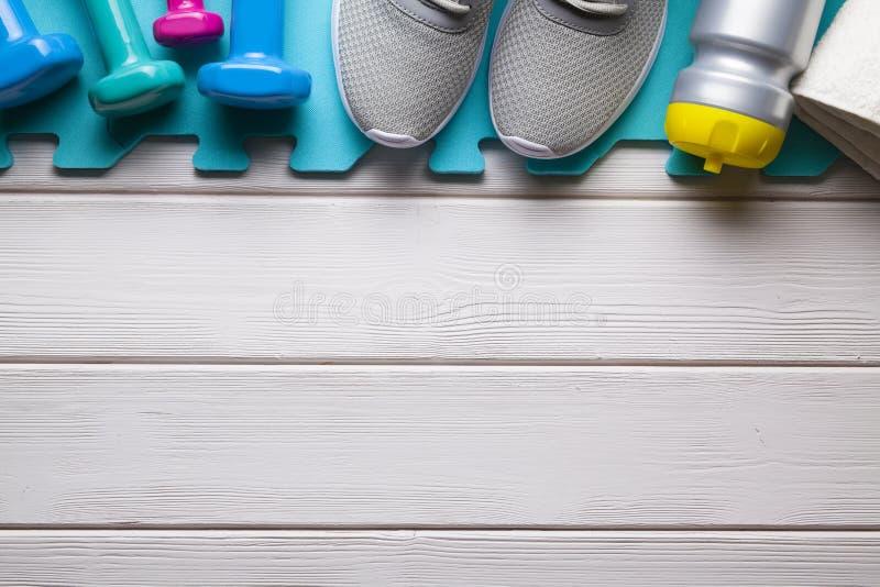 Symbolen en metaforen van sport - fitness materiaal op wit hout stock foto's