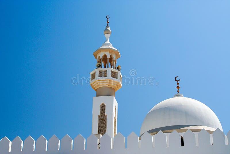 Symbolen van Islam: Witte koepel en Minarette met Islamitisch toenemend maansymbool tegen blauwe hemel in Oman stock foto