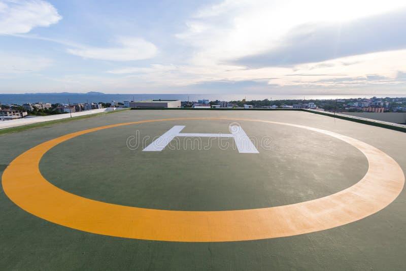 Symbolen voor helikopterparkeren op het dak van een bureaugebouw Lege vierkante voorzijde van stadshorizon Zeehelikopterparkeren royalty-vrije stock foto