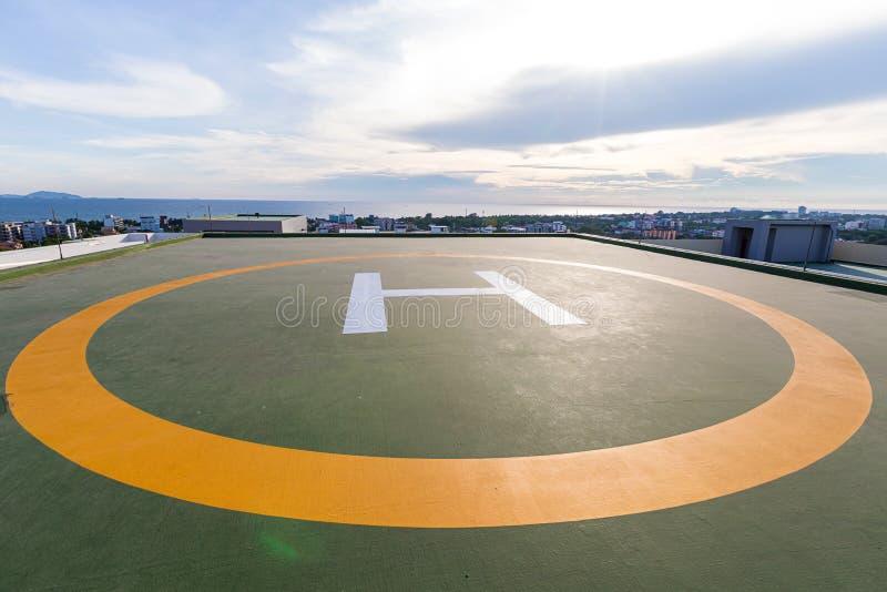 Symbolen voor helikopterparkeren op het dak van een bureaugebouw Lege vierkante voorzijde van stadshorizon Zeehelikopterparkeren stock afbeeldingen