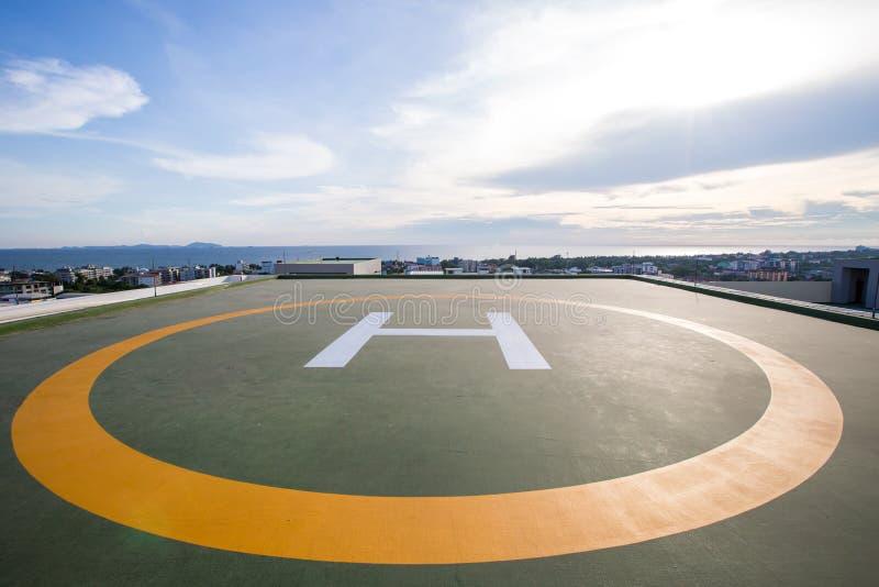 Symbolen voor helikopterparkeren op het dak van een bureaugebouw Lege vierkante voorzijde van stadshorizon stock foto's