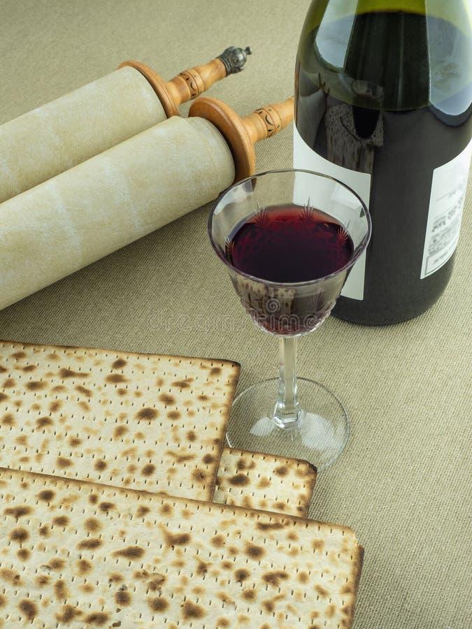 Symboler av den judiska påskhögtiden: Torah snirklar, rött vin i ett exponeringsglas och matzoh på en kanfasbakgrund royaltyfria foton