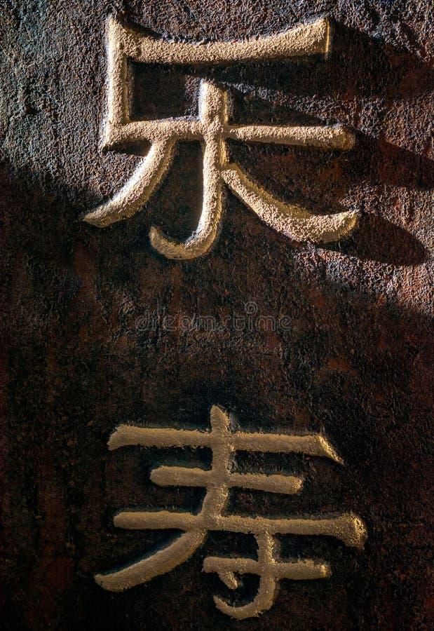 Symboles d'or chinois sur un fond brun image libre de droits