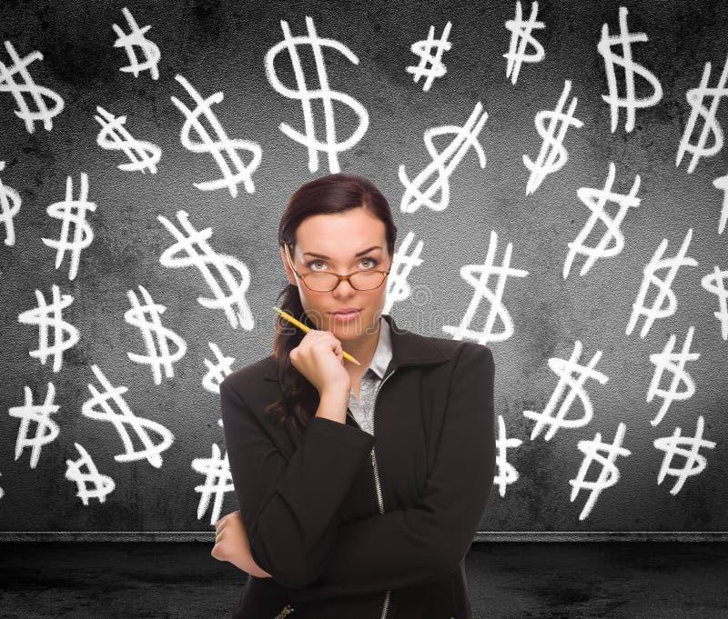 Symboles dollar dessinés sur le mur derrière la jeune femme adulte avec le crayon photo libre de droits