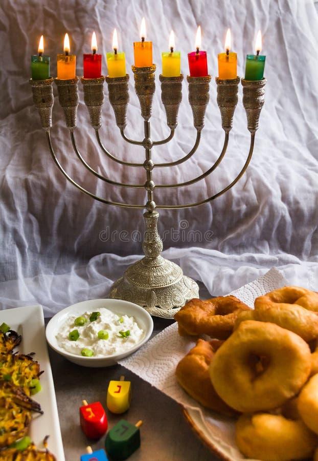 Symboles juifs de Hanoucca de vacances sur le fond blanc ; dessus de rotation traditionnel, candélabres traditionnels de menorah, photographie stock