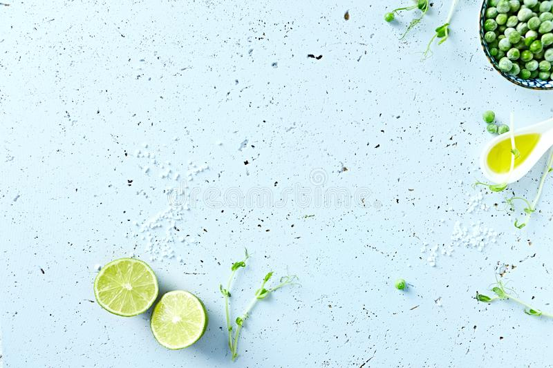 Symbolic food background with lime, pea sprouts, sea salt and frozen peas royalty free stock photo