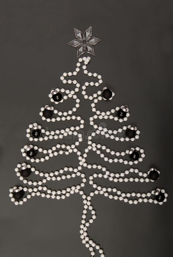 Symbolic New Year`s tree, New-year tree, white beads are on bla royalty free stock photo