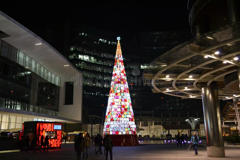 Symbolic plastic Christmas tree wishing Merry Christmas in many main languages. stock image