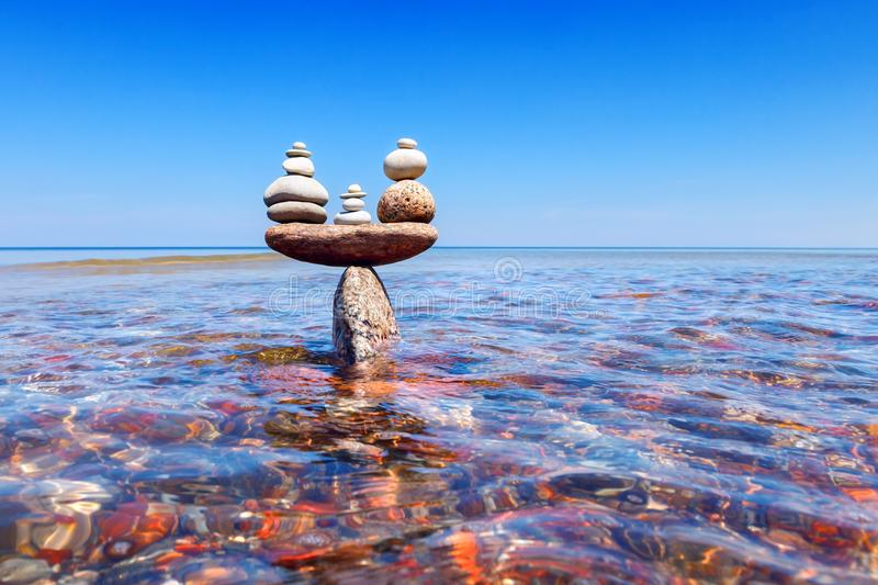 Symbolic scales of standing stones in the water. The concept of balance. Symbolic scales of standing stones in the water. balance and serenity concept stock photo