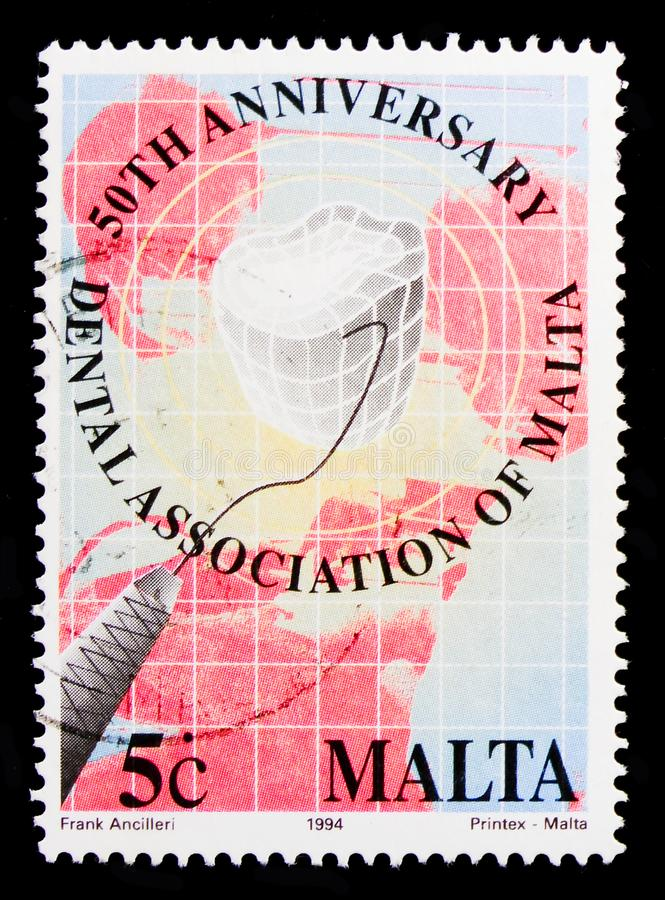 Symbolic tooth and probe, 50th Anniversary of Maltese Dental Associationserie, circa 1994. MOSCOW, RUSSIA - OCTOBER 3, 2017: A stamp printed in Malta shows royalty free stock photo