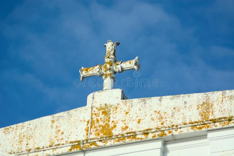 Symbolic White Cross on roof. Old white symbolic religious cross on roof of white building with blue sky royalty free stock image