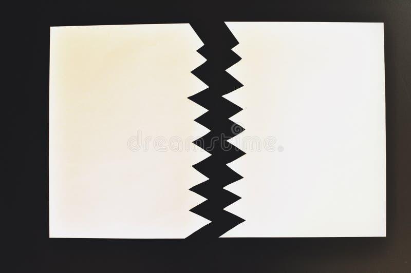 Symboliczny pojęcie dzielący lub oddzielający drzejący papier w dwa prześcieradłach Biała księga rozdzierał w połówce odizolowywa fotografia stock