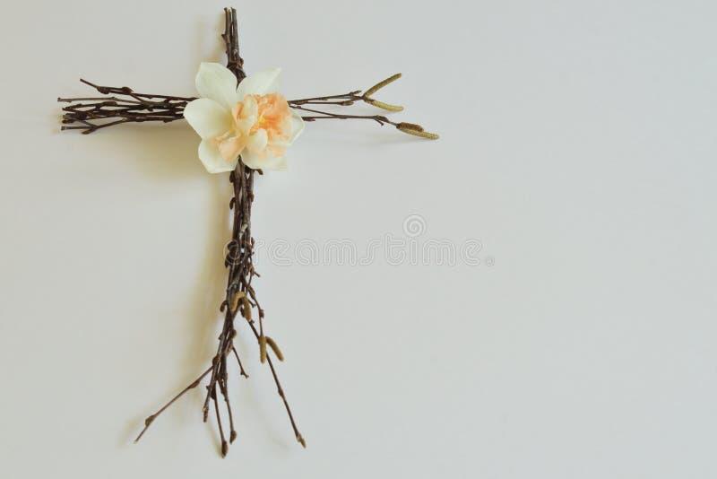Symbolisch concept voor Pasen Het gestileerde die kruis van berk wordt gemaakt vertakt zich met oorringen en gevoelige witte narc stock afbeeldingen