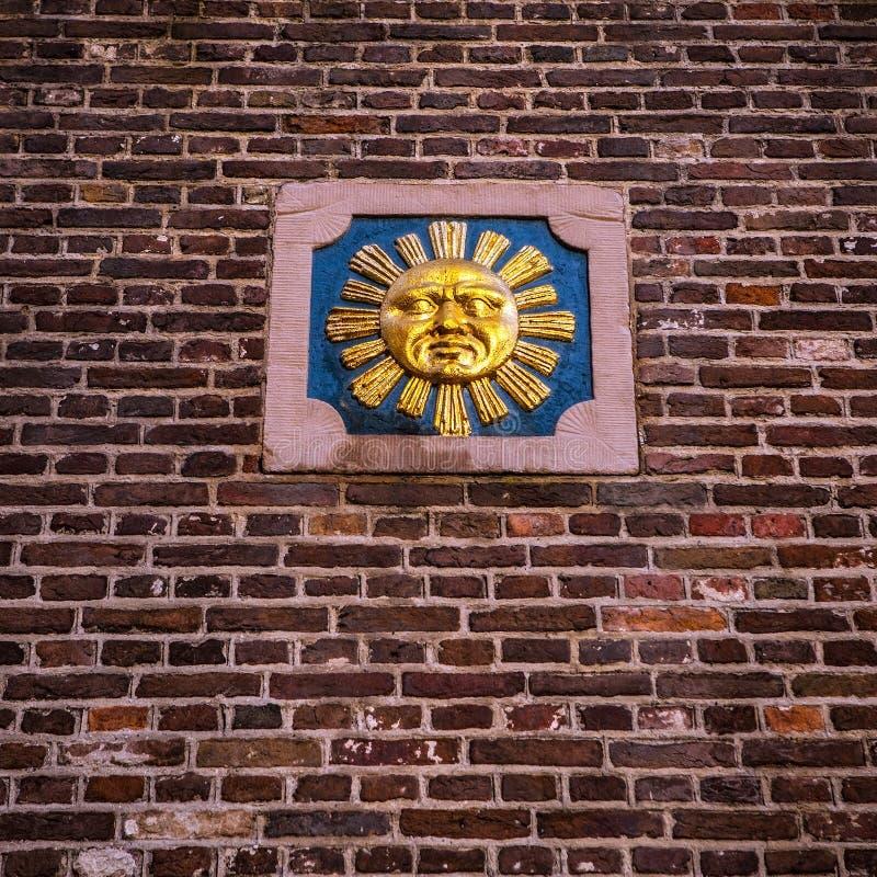 Symbolische Bilder auf einer alten Backsteinmauer des Stadtgebäudes stockbild