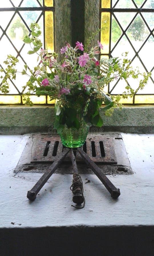 Symbolisk skärm av lösa blommor och korsfästelse spikar, i ett kyrkligt fönster, England arkivbilder