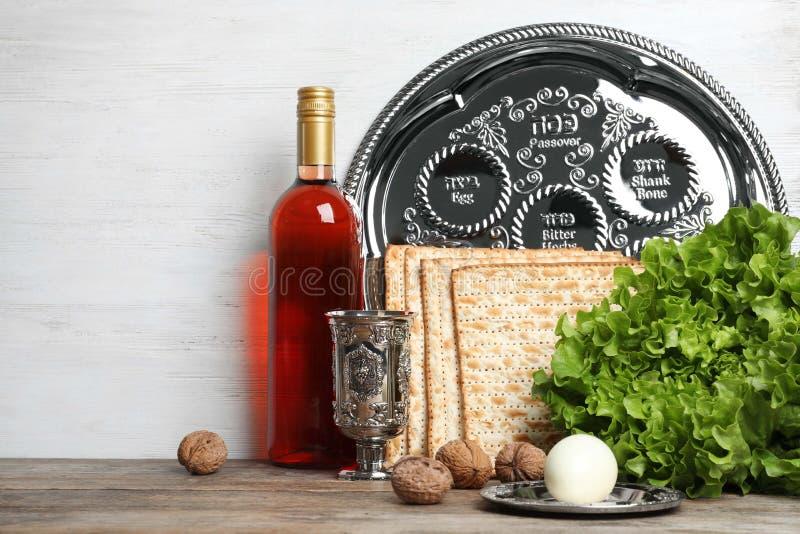 Symboliska påskhögtidPesach objekt på tabellen mot träbakgrund royaltyfri foto