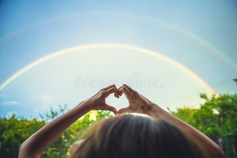 Symbolisme de l'amour, ciel arc-en-ciel, amour. mains en forme de coeur et arc en ciel. double arc-en-ciel image libre de droits