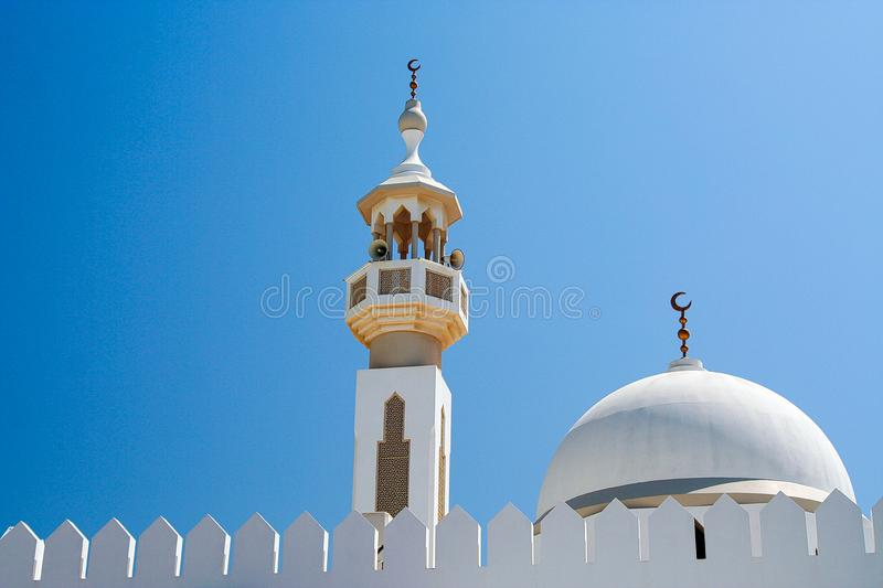 Symbols of Islam: White dome and Minarette with islamic crescent moon symbol against blue sky in Oman stock photo