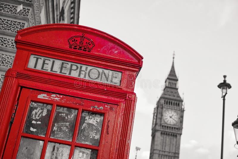 Symbols of London inline with isolated red telephone box. Traditional English telephone box inline with Big Ben in the back, isolated with red stock image