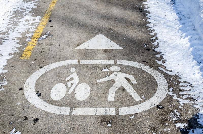 Symbols Painted on Asphalt of a Pedestrian and Bicycle Path. Pedestrian and Bicycle Path Cleared of Snow with a Sign Painted on Asphalt stock photo