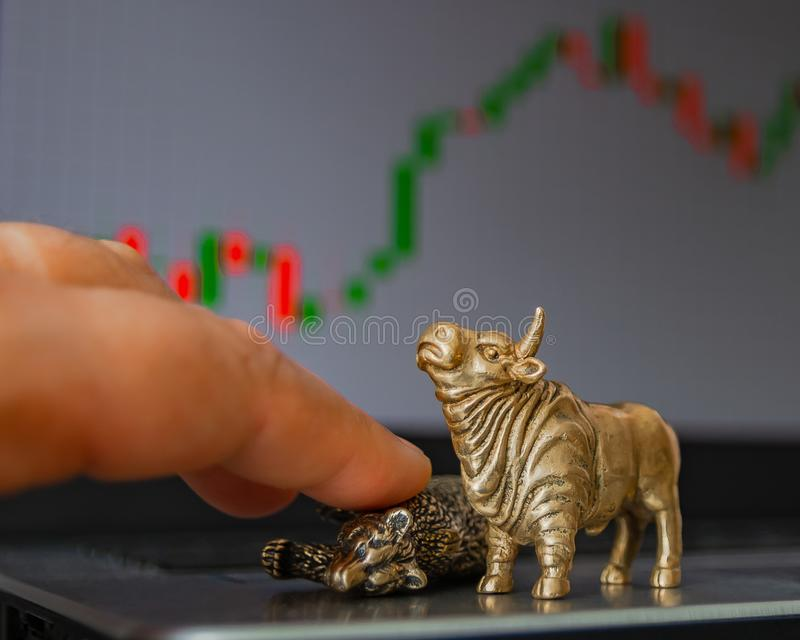 Symbols of stock trading on the background of the trading chart. Bull and bear as symbols of stock trading on a blurred background of price graphics. The stock image