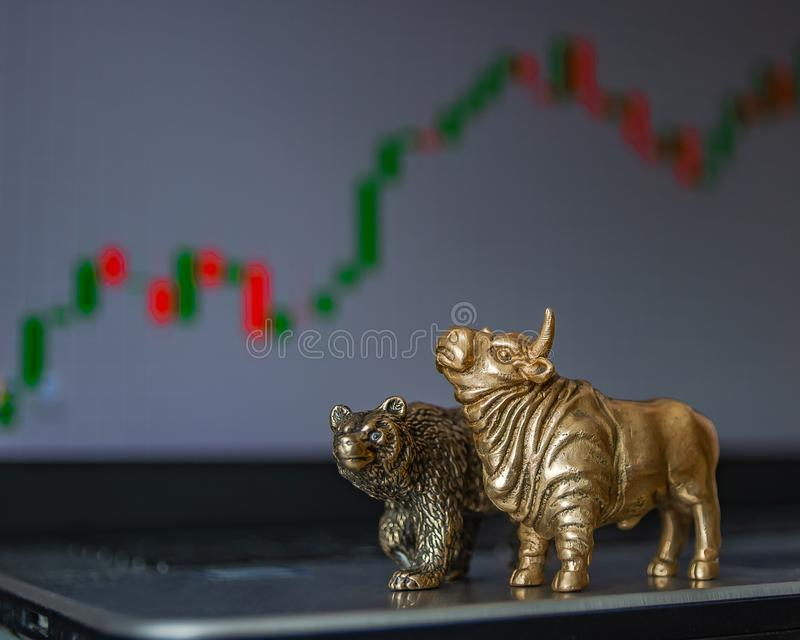 Symbols of stock trading on the background of the trading chart. Bull and bear as symbols of stock trading on a blurred background of price graphics. The stock photos