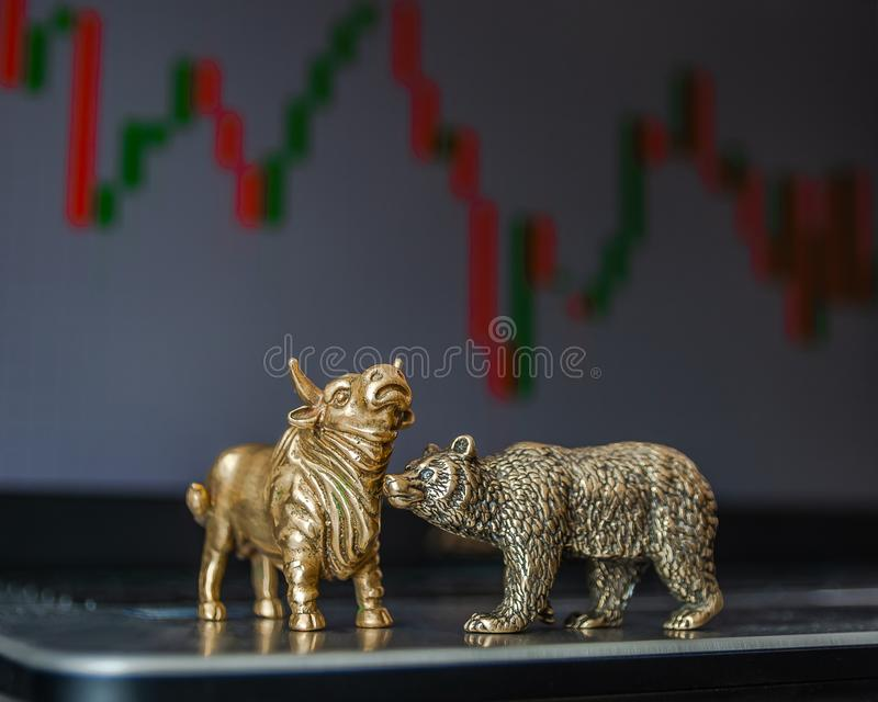 Symbols of stock trading on the background of the trading chart. Bull and bear as symbols of stock trading on a blurred background of price graphics. The stock photo