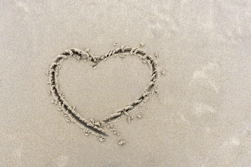 Symbool van hart op zand van strand met de hand wordt geschreven dat stock foto's