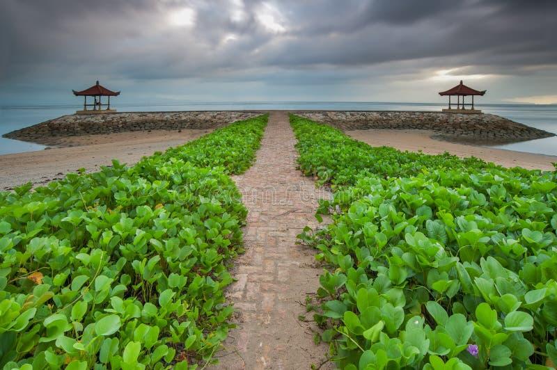 Symetryczny chmurny ranku widok przy Pantai Karang, Bali, z greenery przedpolem zdjęcie stock