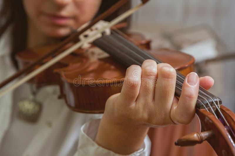 Symfoniorkester på etappen, händer som spelar fiolen Grunt djup arkivfoto
